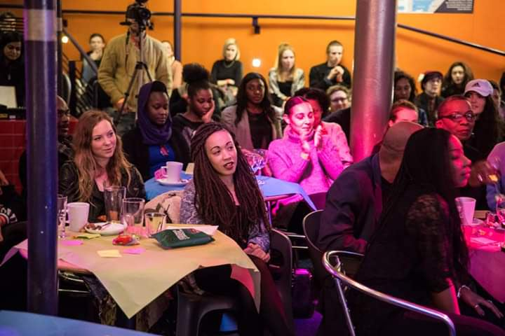 A crowded event space in which the audience, mostly seated at tables, seem to be watching something off-camera. Charlotte, a young black woman with her brown hair in braids, is the focal point of the image.