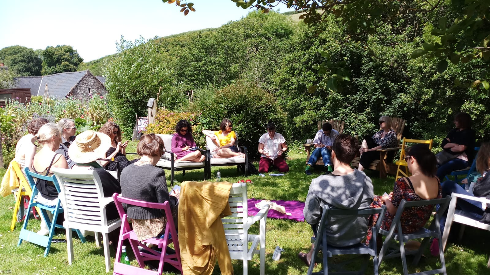 A varied group of people are sat on chairs in a circle, in an outdoor, lush and leafy space, perhaps a park or a garden. Dappled sunlight falls upon them through the surrounding trees. There are about 15 of them, some writing in notebooks whilst the others appear to be talking.