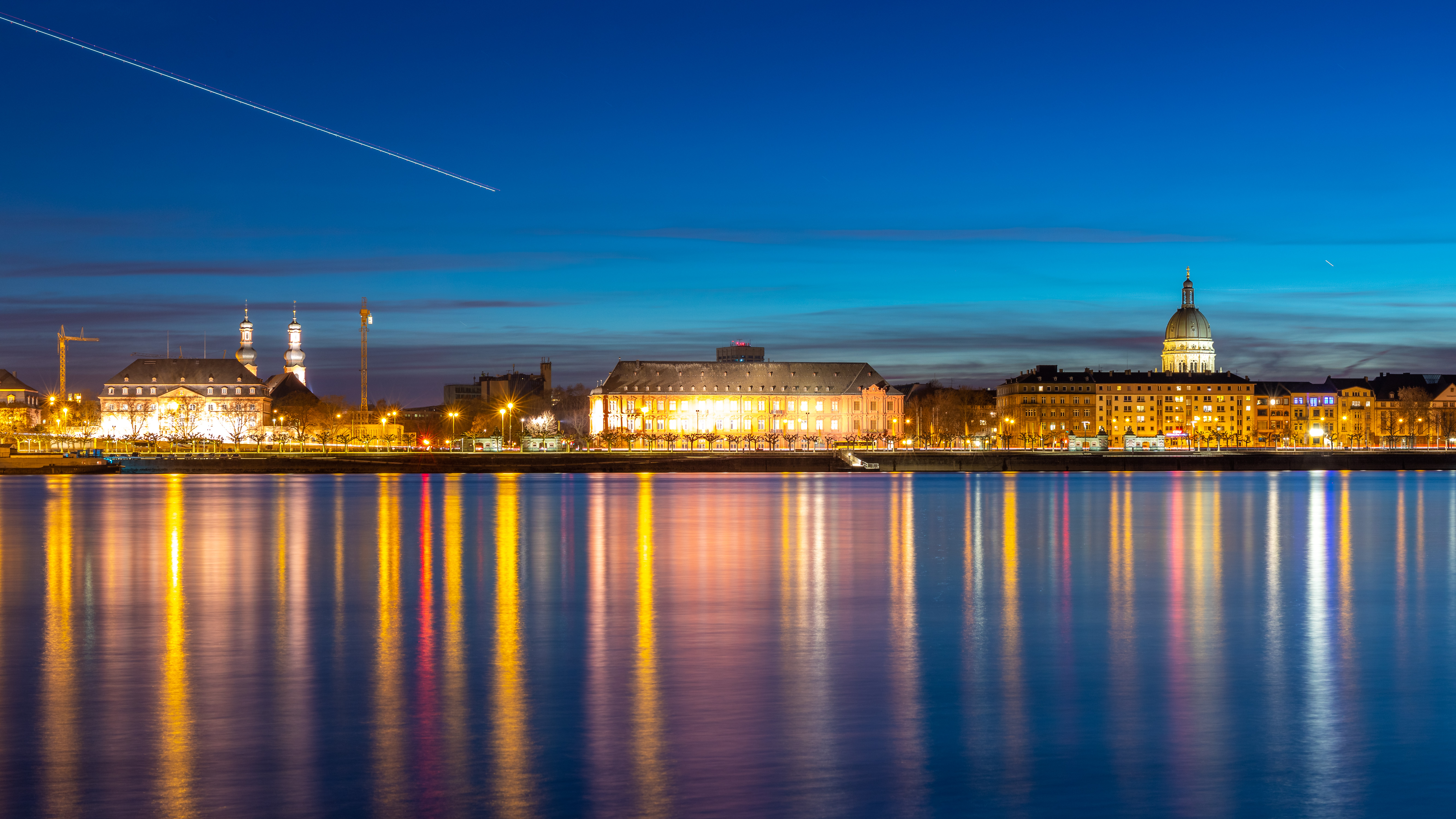 Beautiful sunset image of Mainz. A waterfront composed of buildings and spires is seen beyond a calm body of water in the foreground. The waterfront is lit up in golden tones, which are reflected in the water.