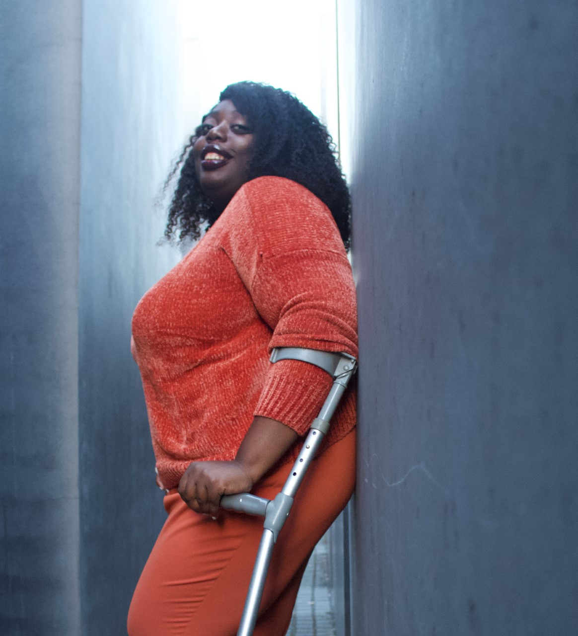 Image of new trainee Mojere Ajayi-Egunjobi wearing an all orange outfit, leaning on a wall and looking at the camera with a smile. She is standing up and supported by forearm crutches.