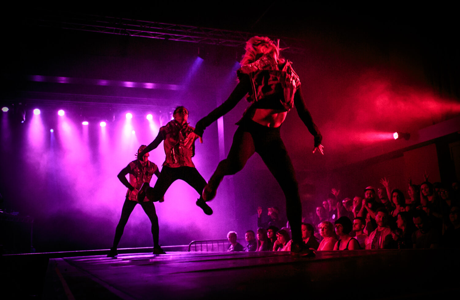 An image of three dancers lined up on a runway-style stage leaping upwards ito the air, their chests pushed forwards and heads thrown back. Audience members are visible to the right of the image and they look on seemingly entranced.