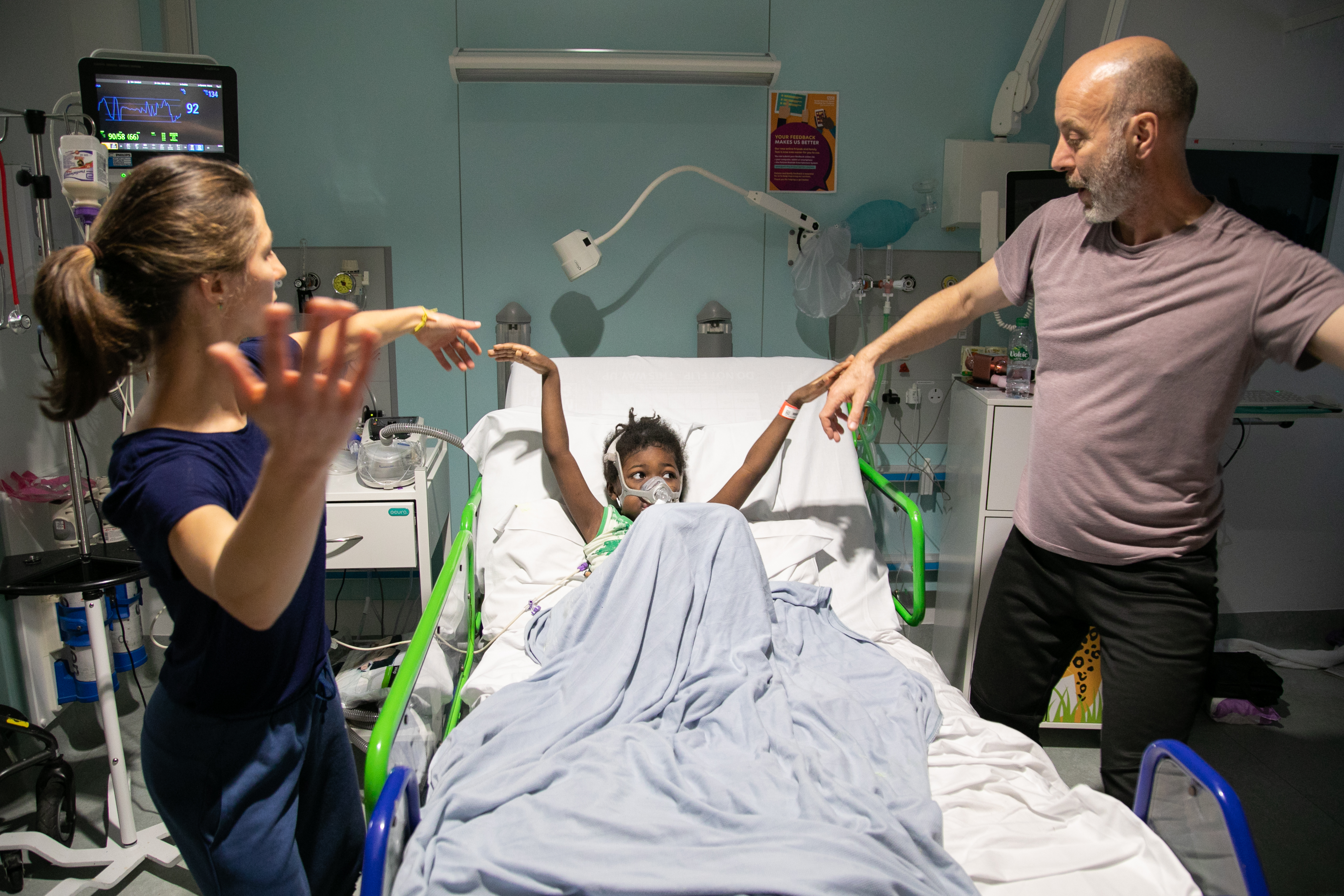 A child lies in a hospital bed with a performer stood on either side of them each holding one of their hands up.