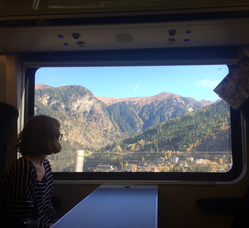 A woman sits staring out of a train window as the train passes through mountains lit by the sun. The sky behind is blue with a single white cloud.