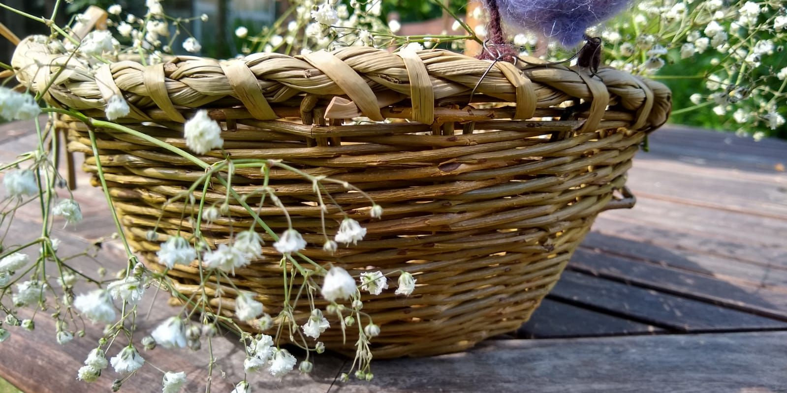 A hand-woven basket sits on the pavement. Out of it spring white and green flowers and fauna.
