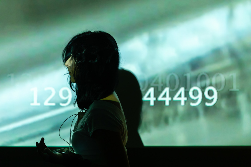 A woman stands in front of a projected image of numbers and technology-like but blurry objects. The image has an atmosphere of loneliness.