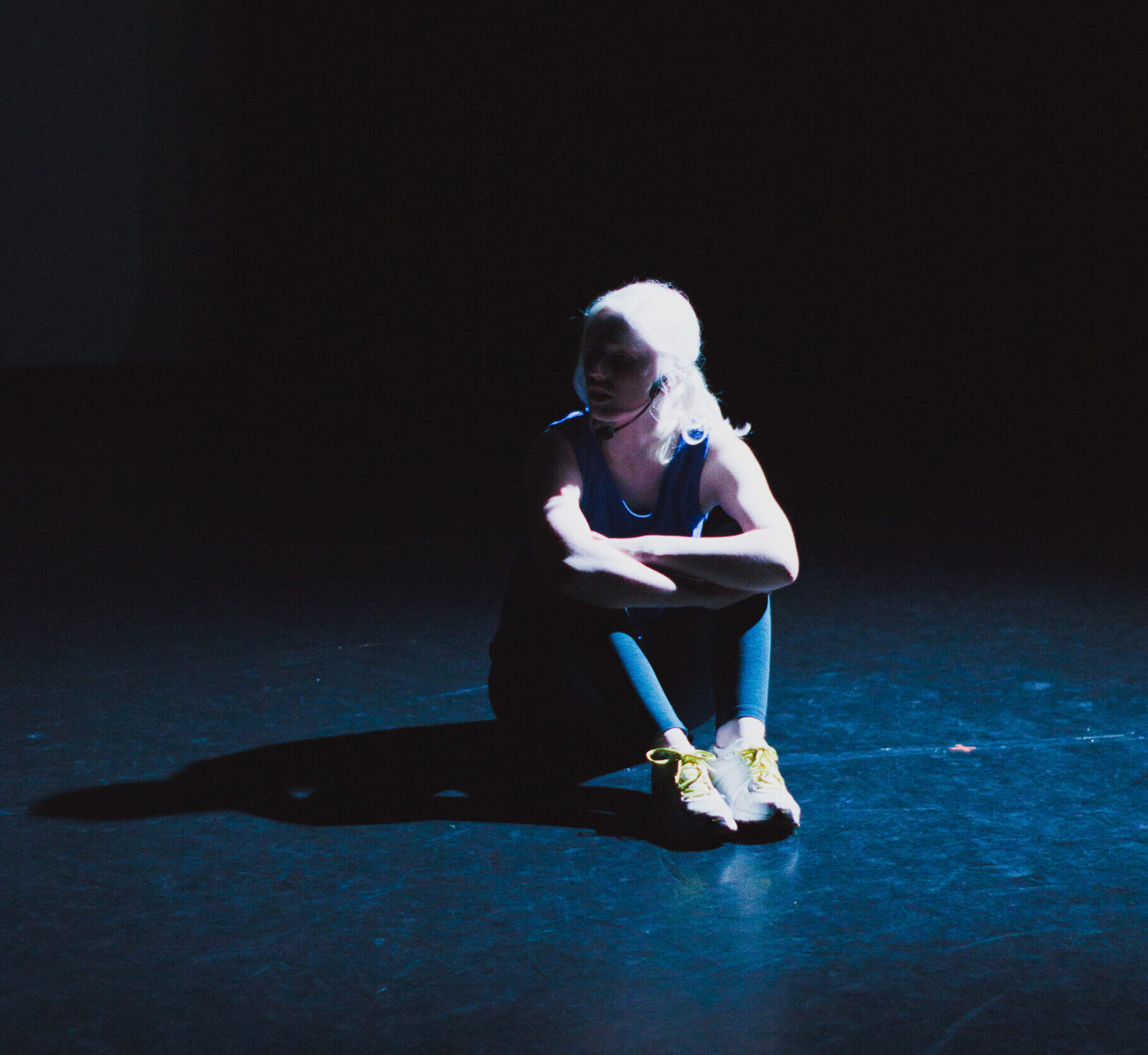 Ellen sits on the floor of the stage, it's dark and she is lit by a spotlight