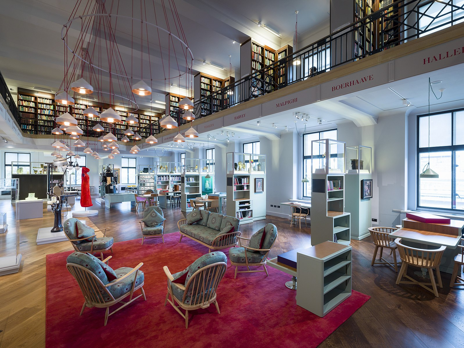 A photo of the reading room in Wellcome Collection. A red carpet with wooden arm chairs surrounded by bookshelves underneath a feature light of red wires and warm yellow lampshades.