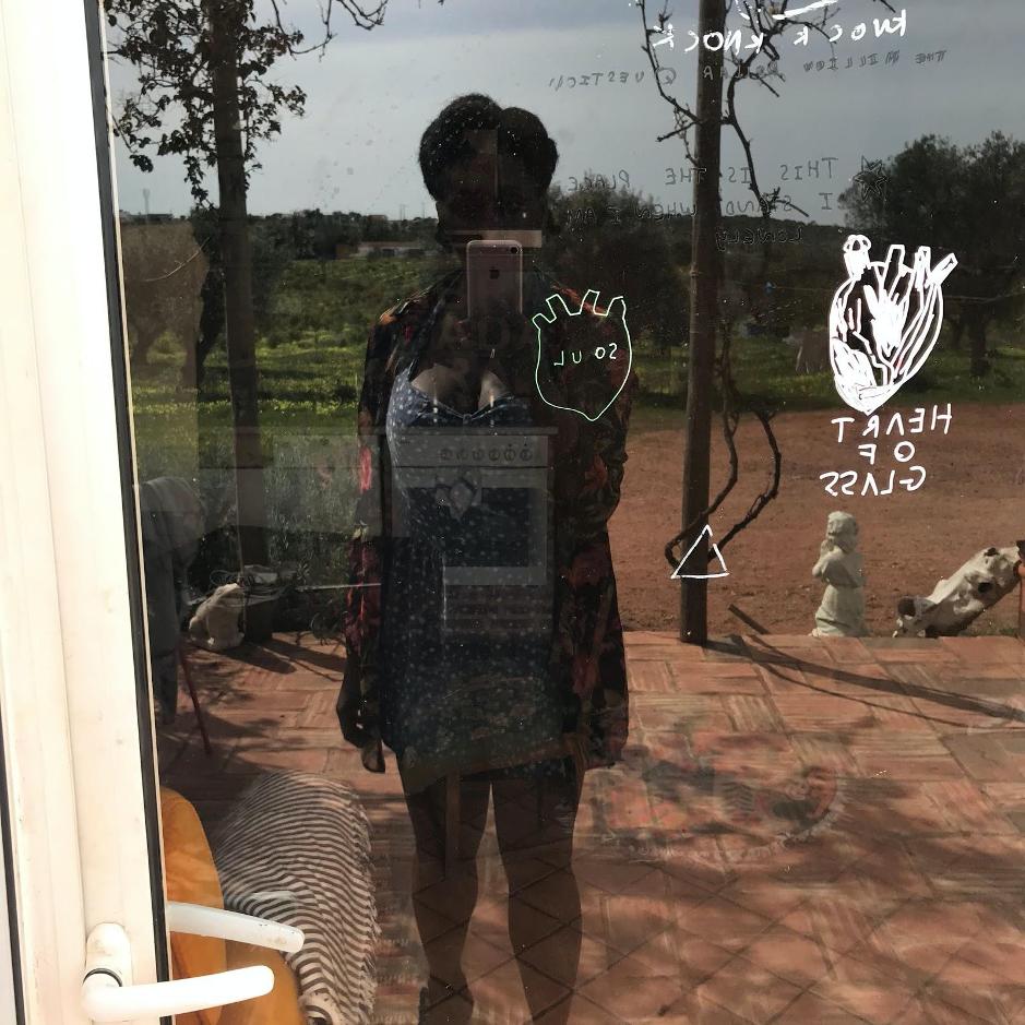 Reflection of artist Nwando Ebizie in a window