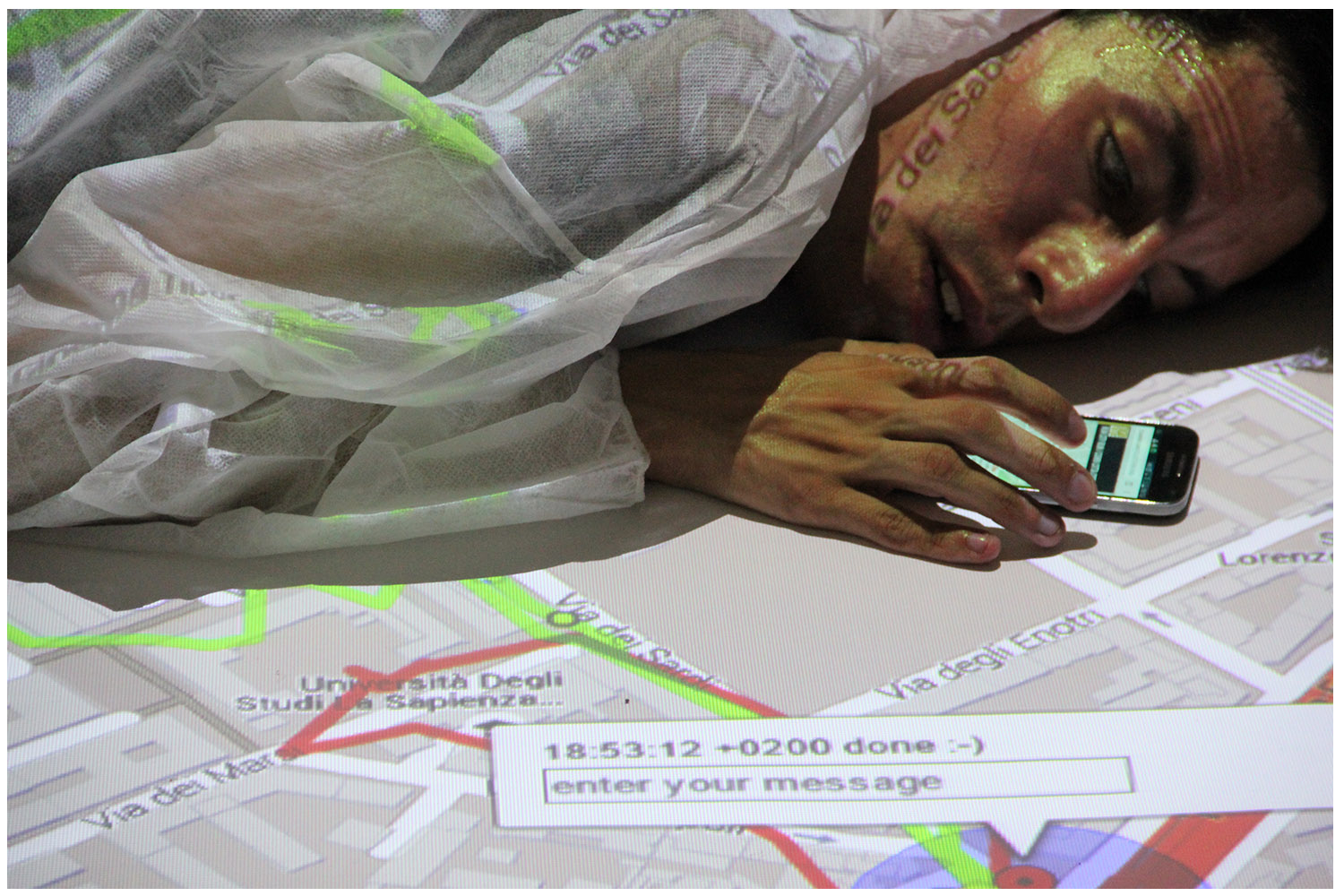 Photograph of a person lying face-down on a projection of a street map. The person is wearing a white protective suit, which is also acting as a projection space. The person has one hand on a mobile phone.
