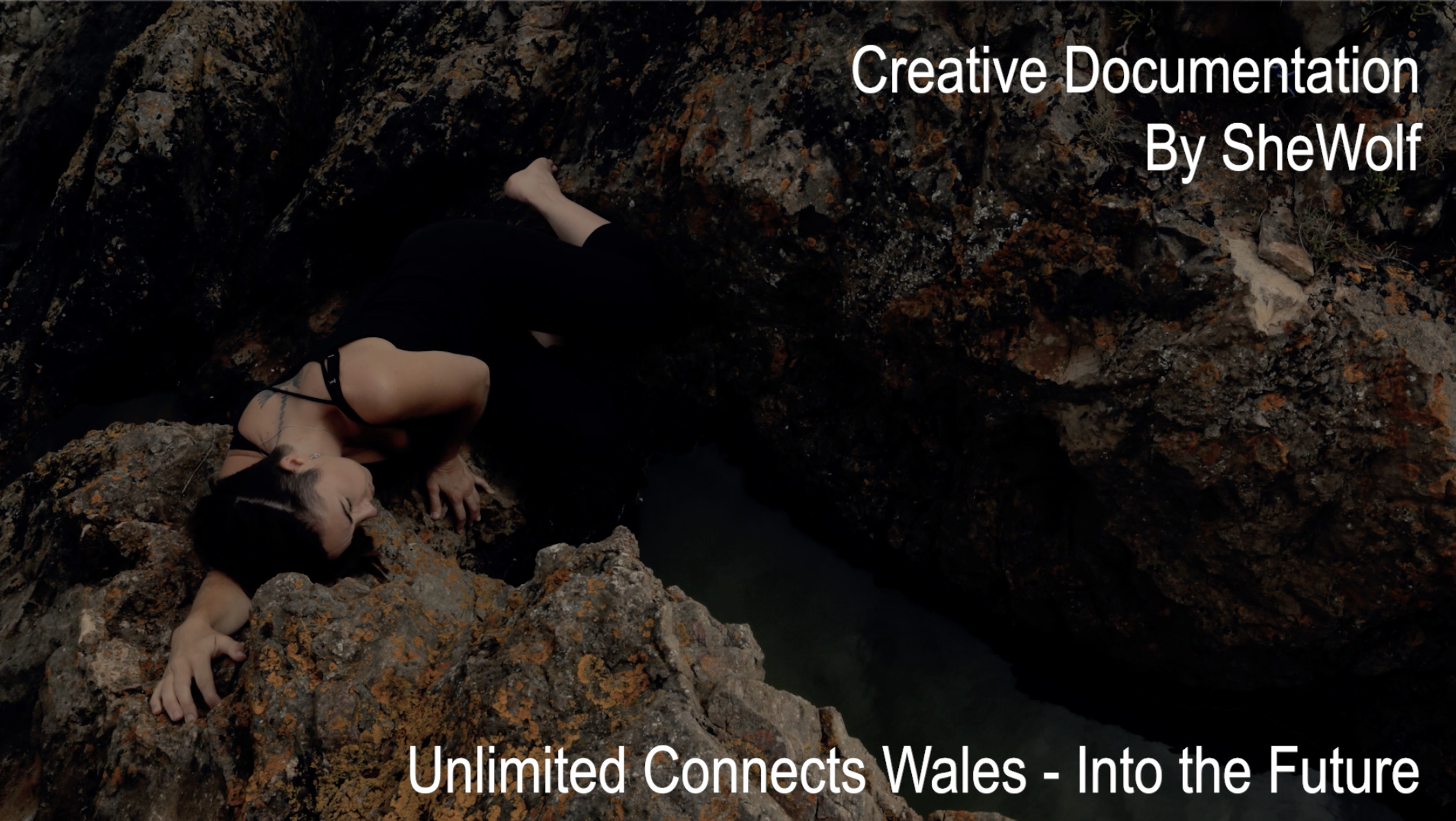 An image of a white woman aged 38 dressed in black leggings and a black vest top lays on her side on top of some deep brown and orange coloured rocks there is a small pool of gathered seawater in the rock. Text is overlaid on the image which reads: Creative documentation By SheWolf Unlimited Connects Wales – Into the Future