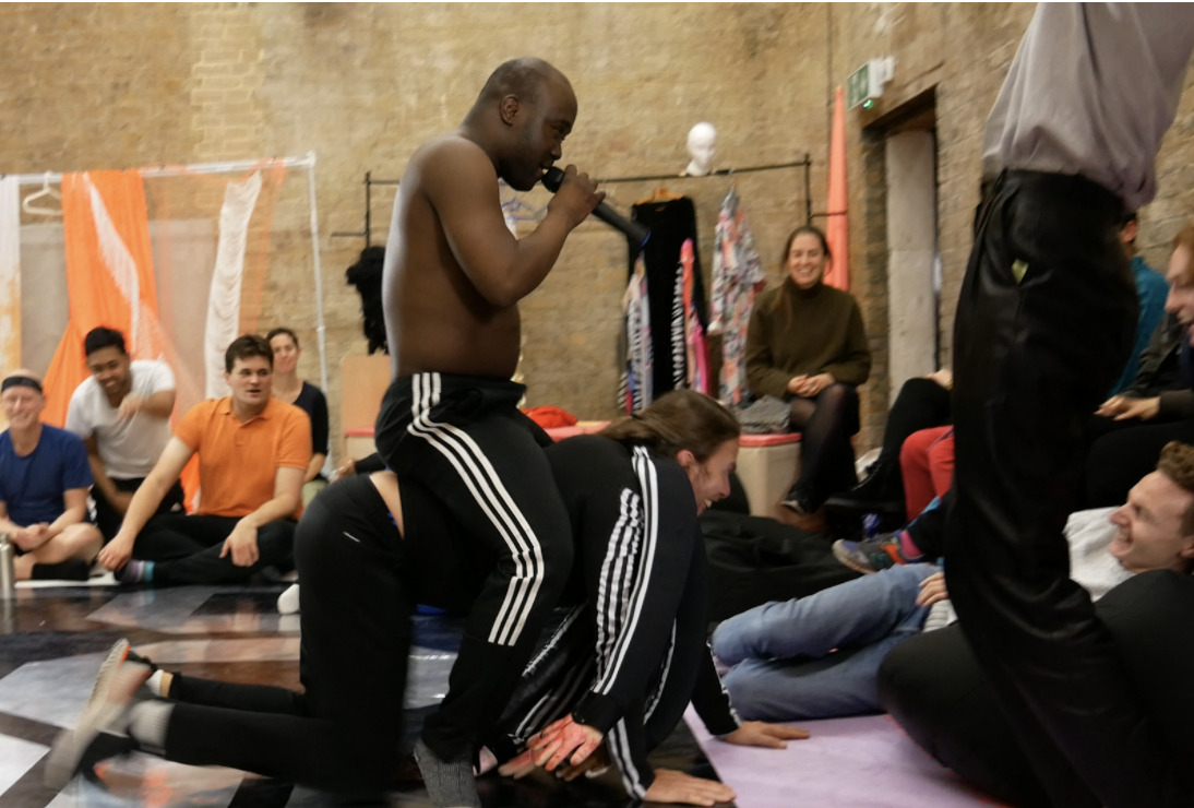 A photograph of a hall in which there are many people. In the background, some people are sat on a bench against the wall. In the foreground, a shirtless man holding a microphone and wearing tracksuit trousers appears to be singing or rapping. There is a large black speaker on the ground in front of him.