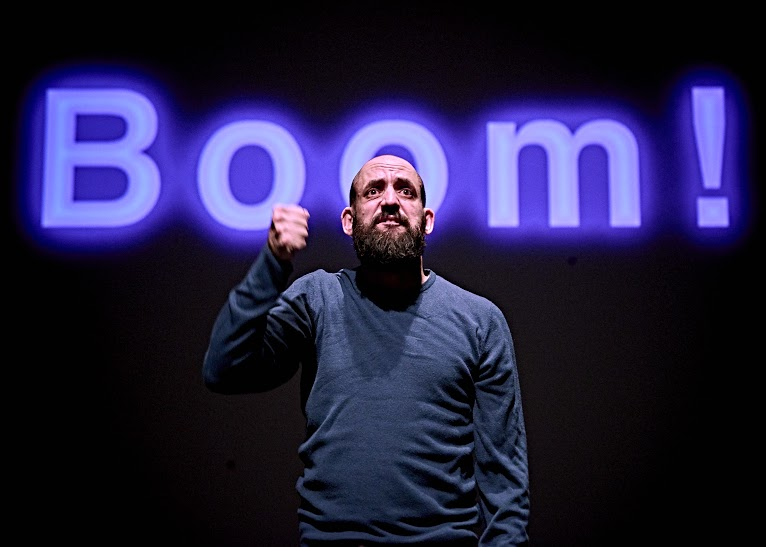 A man stands on stage with his arm raised and fist clenched. Behind him, the word 'Boom!' is projected in big purple letters.