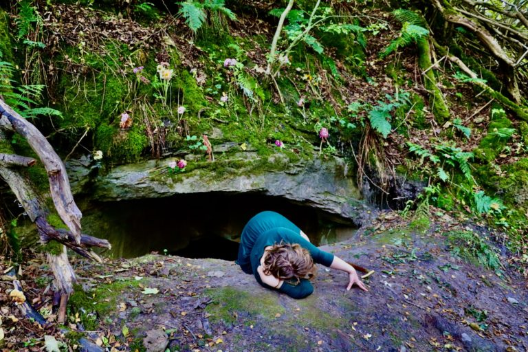 A woman appears to be crawling out of a hole under a tree in a very woody, natural area.