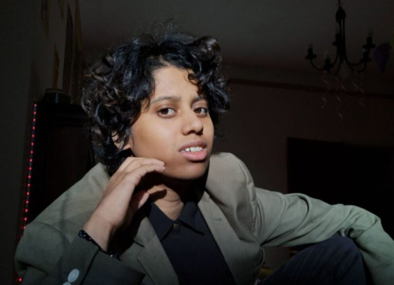 A picture of Marlo. He is young black indian man poses for a photo. His hand is cupped by his cheek and his arm is resting against his leg. His hair is in a shaggy curly mop, that is parted down the middle. He is wearing a olive green blazer and a black shirt.
