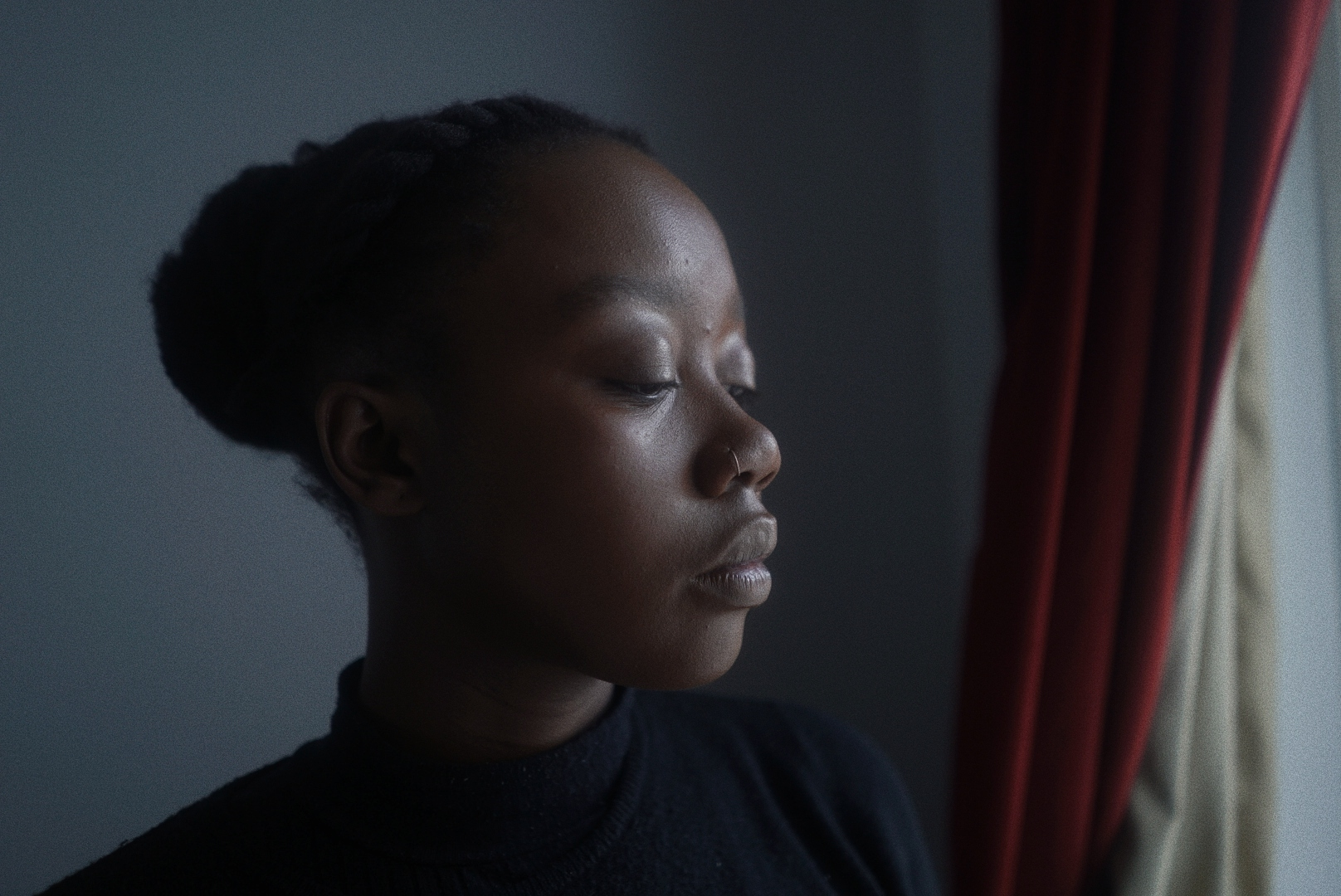 A picture of Jameisha Prescod. A black person wearing a black turtle neck in a greyish room staring out the window.