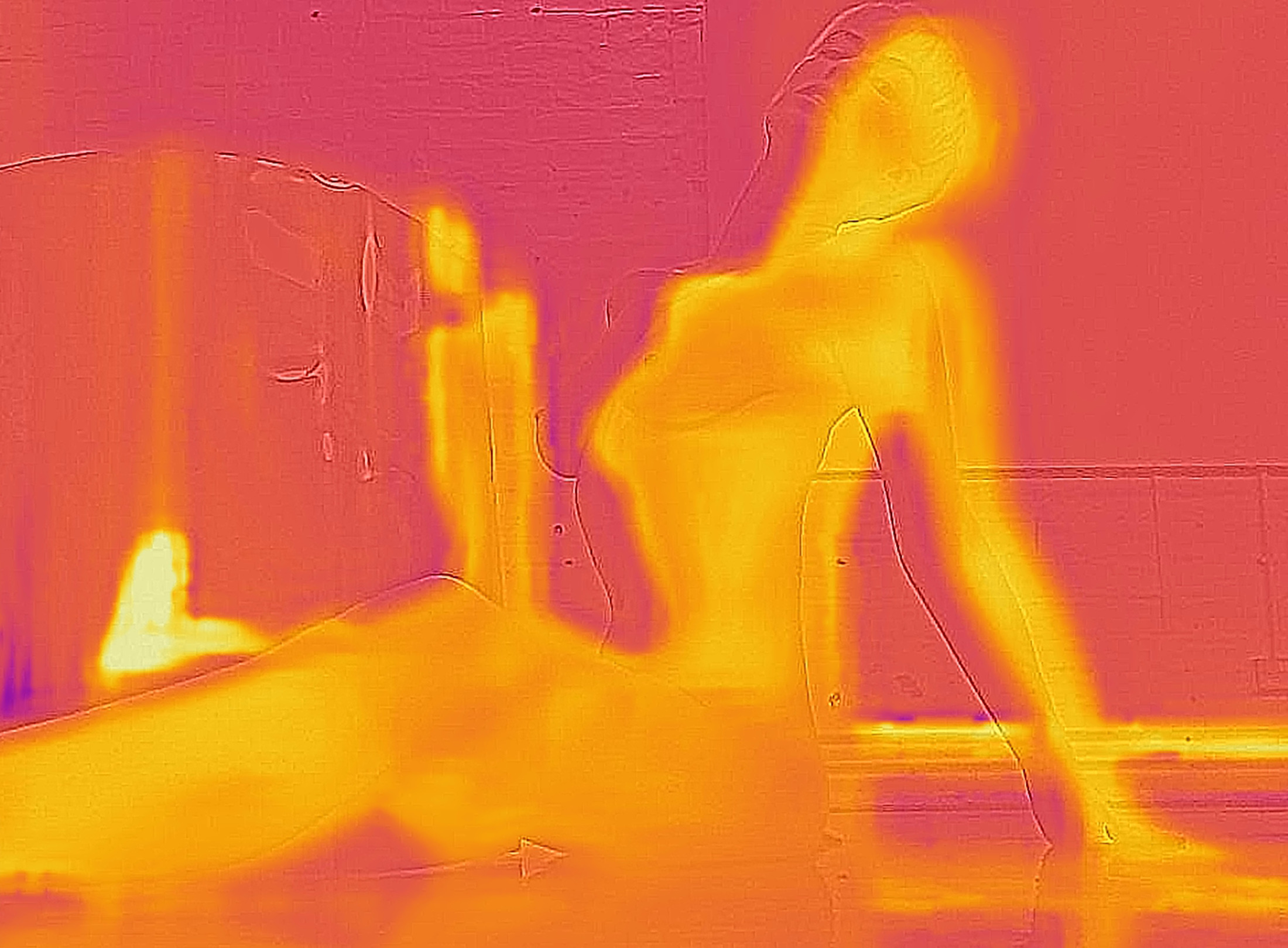 A thermal image showing a dark purple area, which is a studio floor and the shape of a person in orange/yellow signifying their body heat. They are laying on their back on the ground and then roll to the left of the image onto their front. Where they were lying previously there is a yellow shape of a person left on the purple ground, showing the heat their body have left.