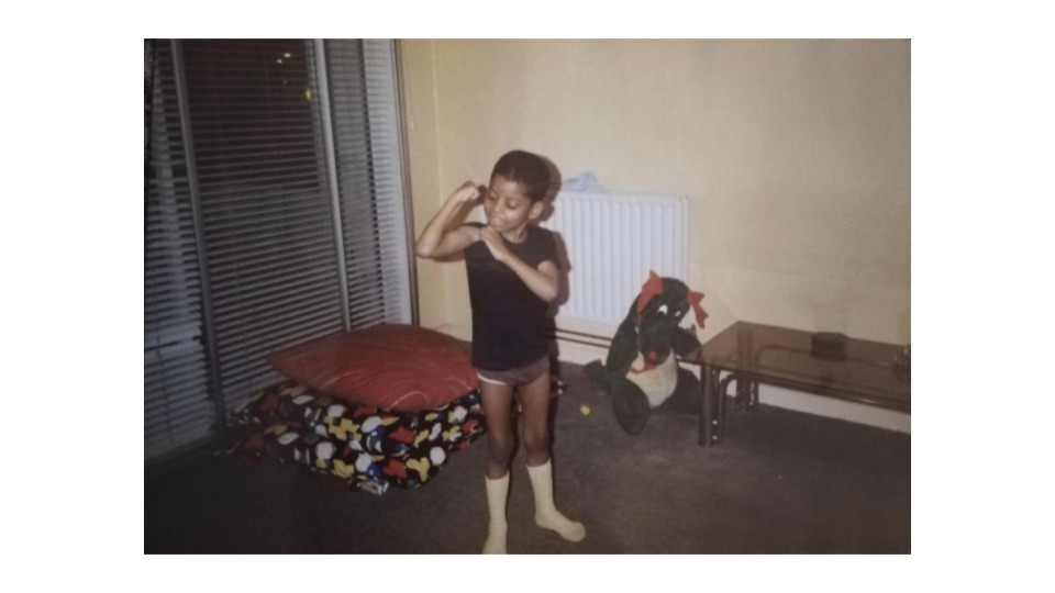 A photo of Christopher when he was a young boy. He's wearing white socks and a tee shirt. He's pulling the sleeve up to his shoulder and seems to be proudly showing off his arm muscles to the camera. In the room there are some cushions on the floor, a green dragon toy and a coffee table. One wall is yellow and the other has blinds pulled down. It appears to be night outside.