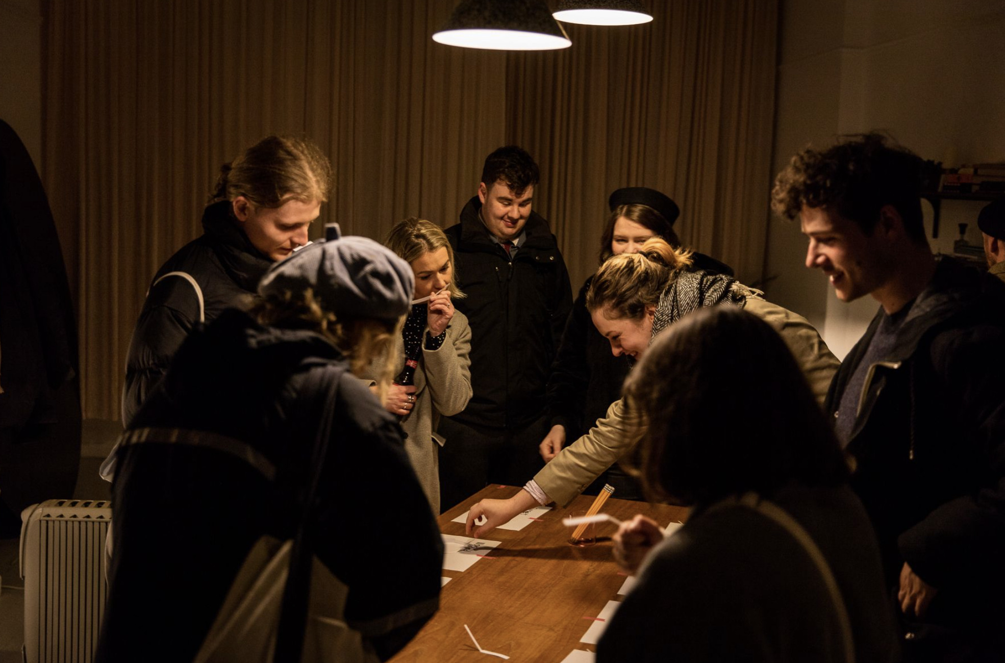 A group of people standing are gathered around a large table. They are smelling different strips of paper and conversing.