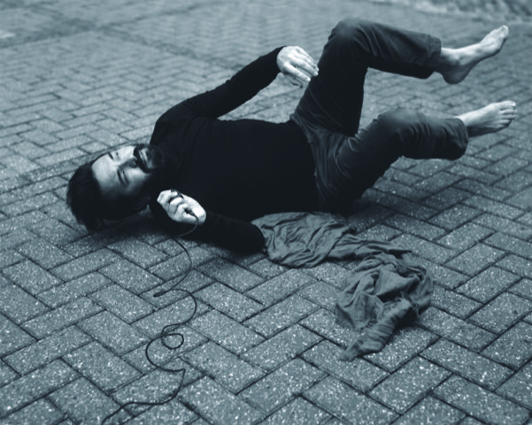 Black and white photo of Juan lying on a bricked floor with their legs and arms in the air.