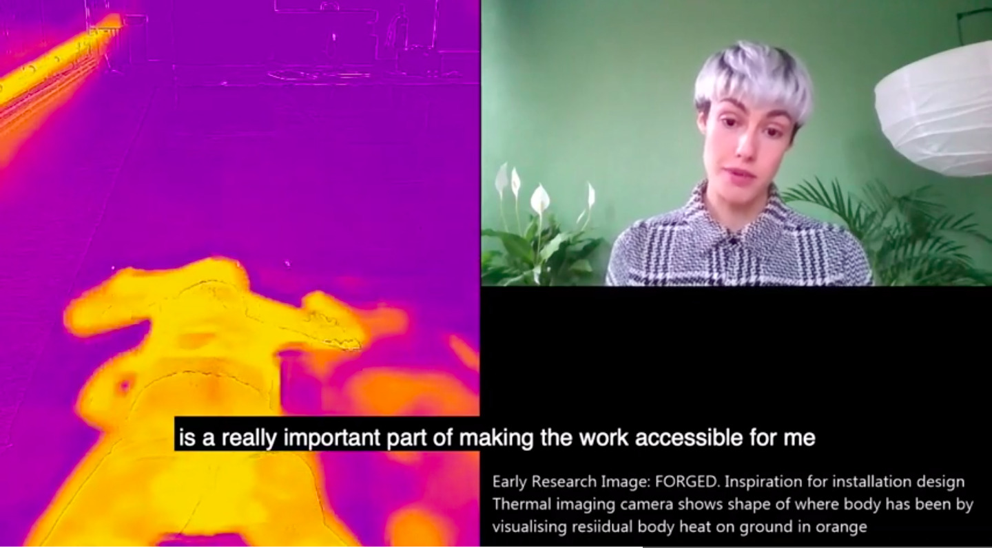 The image is divided into two. The left half shows an heat based reading of Laura's performance, in shades of yellow and purple. On the right, Laura Fisher, a white person with short silver grey hair, is speaking to the camera, sitting in a room with green walls. Captions in the video say: Early Research Image: FORGED: Inspiration for installation design. Thermal imaging camera shows shape of where body has been by visualising residual body heat on ground in orange. Subtitles of what Laura is saying says 'is a really important part of making the work accessible for me'.