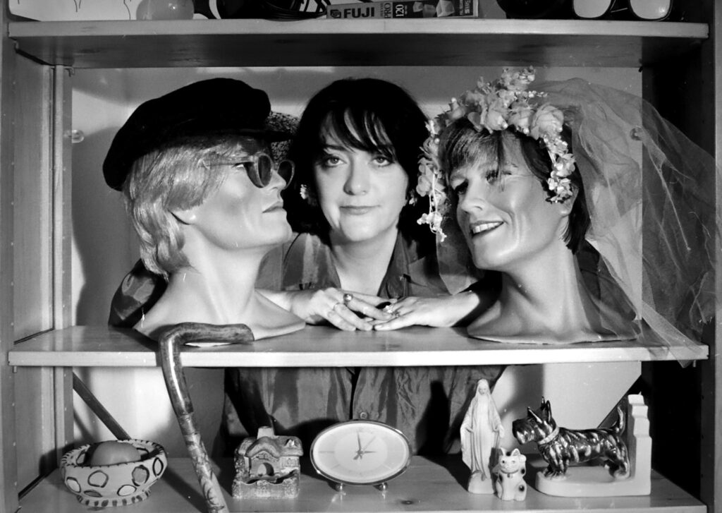 A black a white image featuring Chris next to two mannequin heads. Chris stares into the camera while the mannequins are turned towards her.