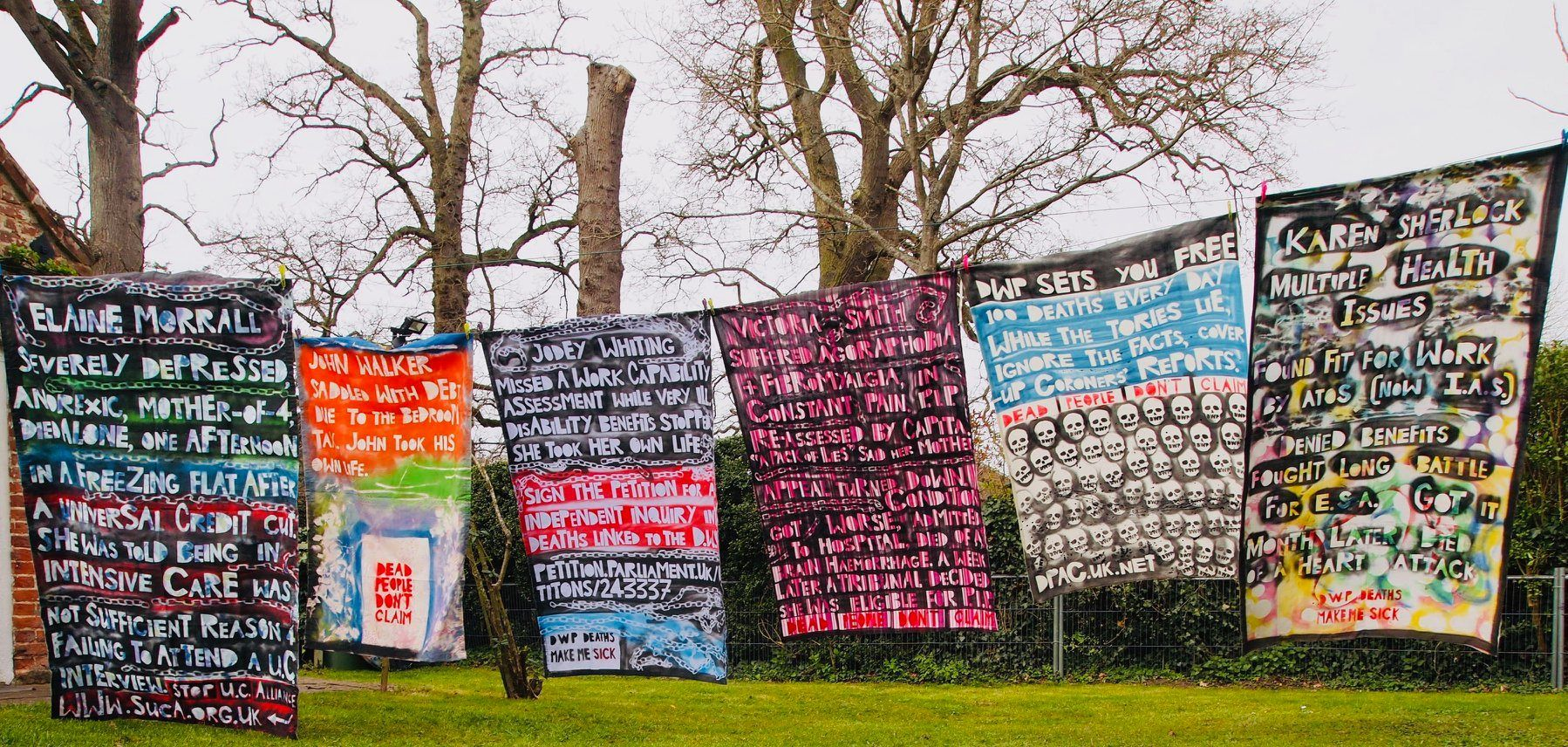 """6 shrouds with painted text hanging in a line outside with trees in the background. They read Elaine Morrall severely depressed, anorexic mother of 4 died alone, one afternoon, in a freezing flat after a Universal Credit cut. Elaine was told being in Intensive Care was not sufficient reason for failing to attend a UC interview. Stop U.C. Alliance www.suca.org.uk John Walker Saddled with debt due to the bedroom tax. John took his own life. 'Dead People Don't Claim.' Jodey Whiting Missed a Work Capability Assessment while very ill. Disability Benefits stopped. She took her own life. Sign the petition for an Independent Inquiry into Deaths linked to the DWP. DWP Deaths Make Me Sick Victoria Smith Suffered agoraphobia + fibromyalgia, in constant pain. PIP re-assessed by Capita. """"A pack of lies,"""" said her mother. Appeal turned down. Condition got worse. admitted to hospital, died of a brain haemorrhage. A week later a Tribunal decided she was eligible for PIP. Dead People Don't Claim DWP SETS YOU FREE 100 Deaths Every Day While The Tories Lie, Ignore the Facts, & Cover-Up Coroners' Reports. Dead People Don't Claim. DPAC.UK.NET Karen Sherlock Multiple health issues. Found Fit For Work by Atos (now I.A.S.) Denied benefits. Fought long battle for E.S.A.. Got it. Month later died of a heart attack."""